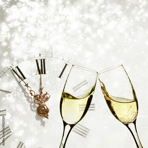 Glasses with champagne andclock against holiday lights