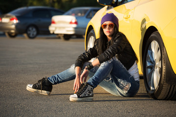 Fashionable punk woman sitting on the car parking