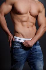 trainierter Mann zieht sich Hose an