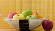 Red apple next to apple basket with yellow background