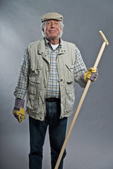 Smiling senior gardener man with hat holding hoe. Studio shot ag