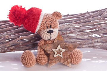 christmas teddy bear on a branch with red hat and scarf