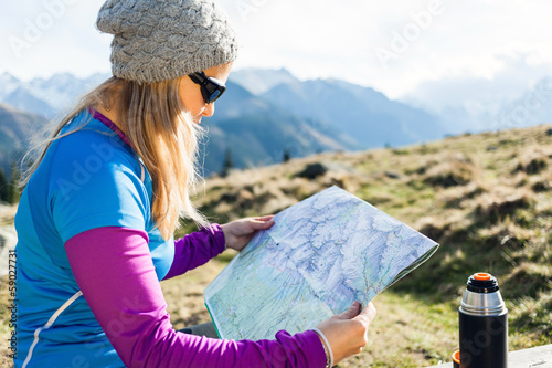Woman reading map in mountains