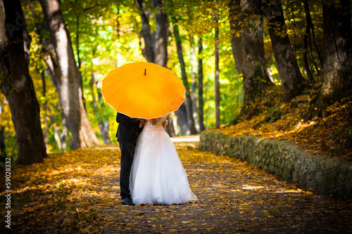 Young married couple in love kissing under umbrella