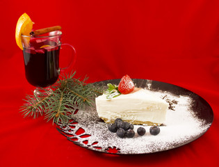 Christmas mulled wine and cheesecake with berries on red