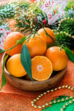 Tangerines in bowl with Christmas decorations