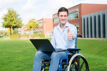 Rollstuhlfahrer mit Notebook zeigt Daumen