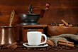 Coffee cup and metal turk on wooden background
