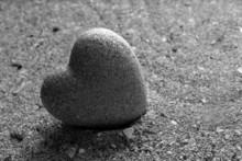 Szary kamień w kształcie serca, na tle piasku