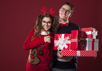Smiling couple holding stack of christmas gifts