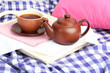 Cup and teapot on wooden tray on fabric background