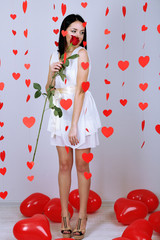 Attractive young woman with rose and balloons in room
