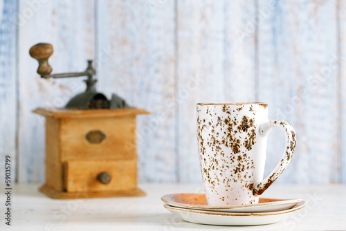 latte coffee cup with Nostalgic coffee grinder on background