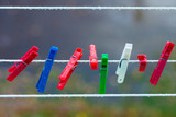 Colorful washing laundry clips on strip outdoor. Background.