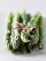 green asparagus garnished with magenta beet sprouts.