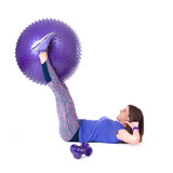 Sport woman exercising with a purple pilates ball and dumbbells