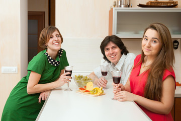 Three young people drink wine