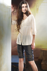 girl with long hair is in fashion style posing on wooden floor