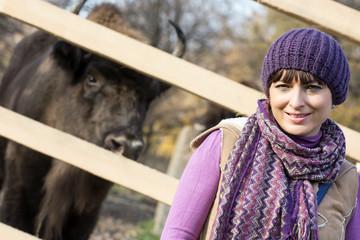 Portrait of a woman with the European bison (Bison bonasus) behi