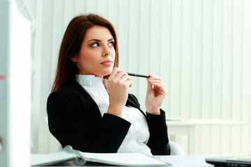Young pensive businesswoman looking away at copyspace in office