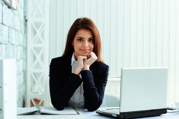 Young cheerful businesswoman sitting at the table