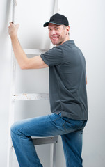 Smiling worker man hold a ladder on a white background