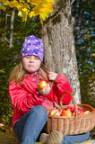 Cute young girl eating fresh autumn apples