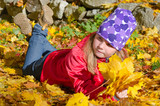 Happy young girl laying on autumn leaves