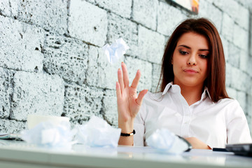 Young frustrated businesswoman throwing paper on table