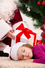 Close up of sleeping little girl under Christmas tree.