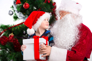 Old Santa Clause and young little boy holding gift box together