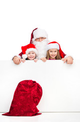 Santa Claus and two kids standing behind white blank poster.