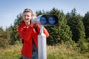 Woman with sightseeing binoculars lookina t camera
