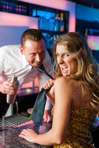 Woman dragging barkeeper in club or bar