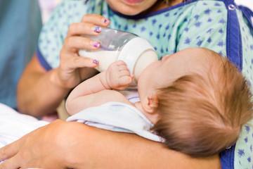 Mother Feeding Milk From Bottle To Newborn Baby