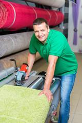 mitarbeiter schneidet teppich von der rolle