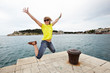 Young cheerful woman jumping on the pier