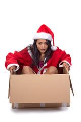 Beautiful woman in Santa Claus dress inside paper box