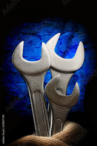 Metallic wrenches in male hand