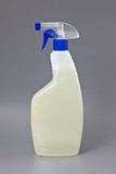 Transparent detergent plastic spray bottle isolated on gray