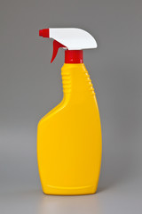 Yellow detergent plastic spray bottle isolated on gray