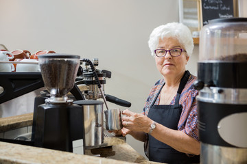 Senior Woman Steaming Milk with Espresso Machine