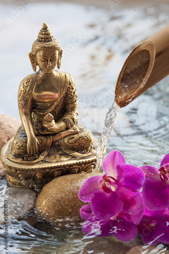 meditating Buddha with flower and water