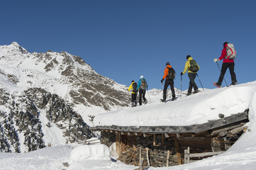 Snowshoers on a roof of a hut