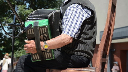 pensionary playing accordion outdoor stage sitting on chair