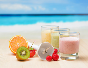 Fruit smoothie on wooden table on tropical beach
