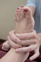 Chiropractor massage foot with both hands client