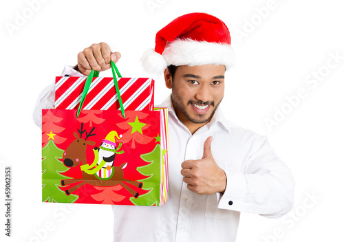 Happy christmas man holding gift bag, giving thumbs up