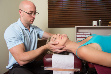 Chiropractor adjusting head muscle female patient
