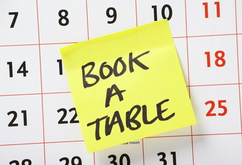A reminder to Book A Table stuck on a wall calendar